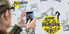 Frau mit Smartphone fotografiert beim DGB-Digitalisierungskongress 2015 ein Graphic Recording Poster