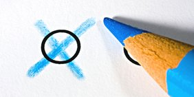 Blauer Buntstift auf Wahlzettel neben Kreuz